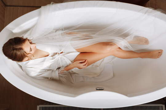 Morning of the bride. Happy beautiful young woman is wearing in a white long veil, robe and underwear sitting laughing and having fun in the bath on a white background, relax. wedding day
