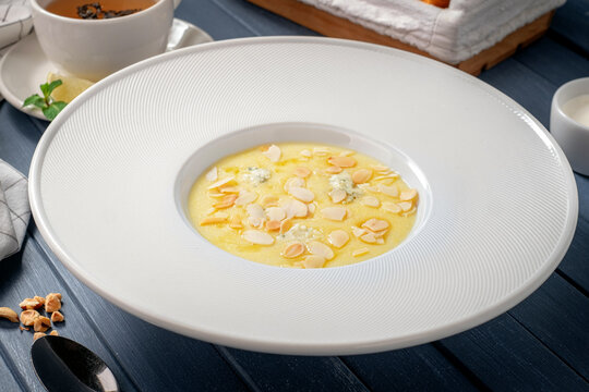 Corn porridge (polenta) with almonds and gorgonzola cheese in a white plate. Healthy breakfast