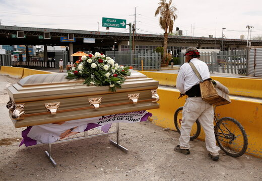 """A man passes by a coffin that was used by Carlos Mayorga, a Mexican candidate for federal representative as part of his campaign slogan """"If I don't deliver, let them bury me alive"""" near the Zaragoza-Ysleta international border bridge in Ciudad Juarez"""