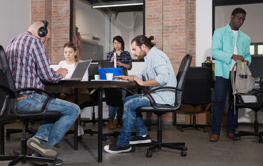 Multiethnic startup business team working on new project in loft style coworking space..