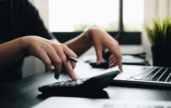 Close up hands businessman doing finances with using calculator and laptop computer in office