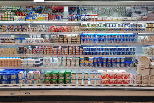 Interior view of huge open refrigerator with various brands of yogurt on the shelves in Jaya Grocery store. Yogurt is a food produced by bacterial fermentation of milk. PENANG, MALAYSIA - 26 MAR 2021