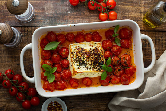 Baked feta cheese with cherry tomatoes in a pan