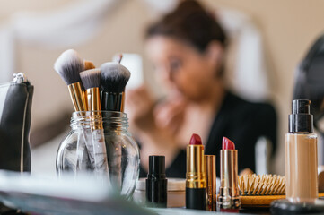 Lipsticks on a wooden table and in the background a woman putting on makeup