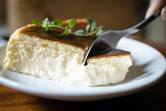 Close Up,Basque Burnt Cheesecake,Tarta de Queso or San Sebastian Cheesecake on a white plate with a spoon to scoop the soft cheese cake,delicious spanish dessert recipe,sweet food made with cream