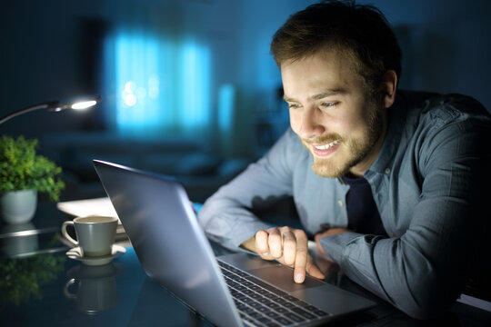 Happy man using laptop in the night at home