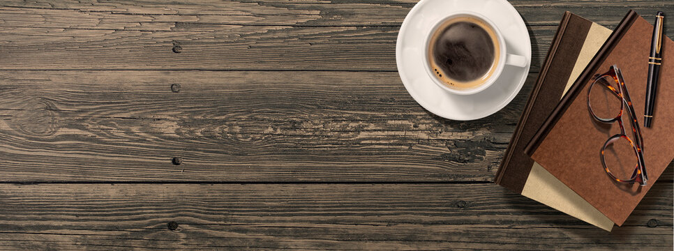 アンティークなテーブルの上にあるコーヒーと本、眼鏡、万年筆。真上からのアングル