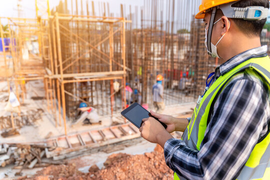 Construction civil engineer or architect with hardhat on construction site checking schedule and building foundations project on tablet computer at construction site