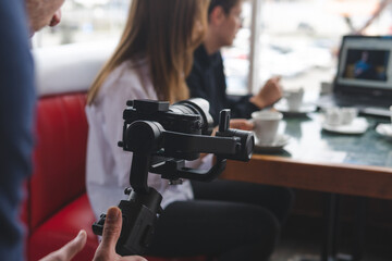 Fototapeta three-axis stabilizer with camera. The operator is in the process of shooting. Equipment. The work of a videographer. Cafe