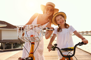 Cheerful mother and daughter on bicycles enjoying summer holidays