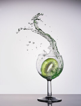 a wine glass into which a kiwi falls and causes a large splash