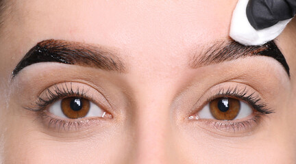 Beautician wiping tint from woman's eyebrows on white background, closeup