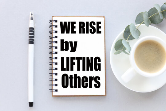 We rise by lifting others. text on white notepad paper. near cups with coffee and plants on a gray background.