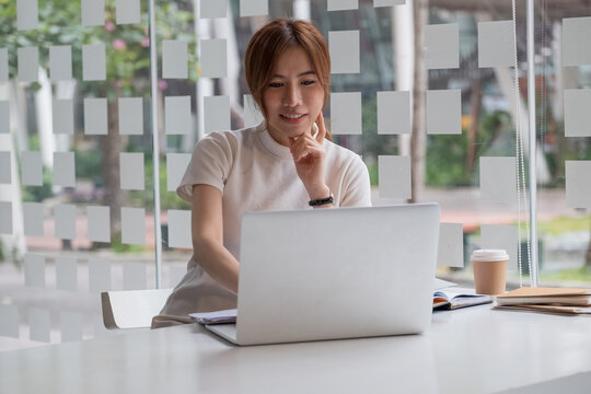 Portrait of asian female working with laptop computer for online business or education concept.