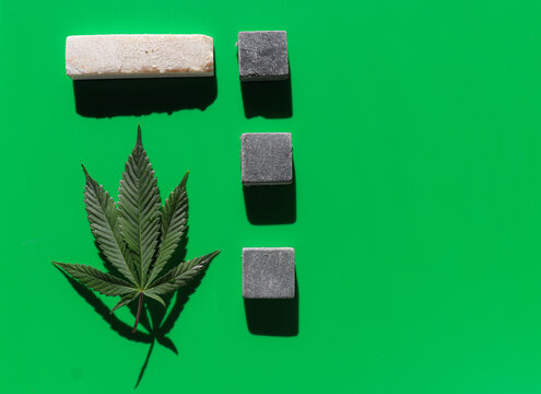 Cannabis leaves on a flat green background with natural geometrical shape marble stones. Poster minimal concept with copy space.