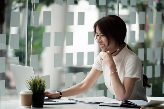 Happy asian woman using laptop computer for video conference. Online business education concept