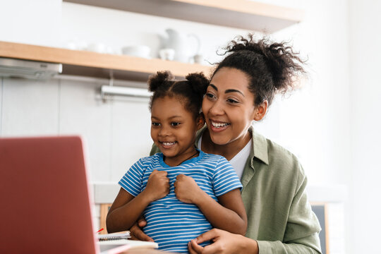 Black smiling woman making fun with her daughter while using laptop