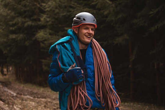 male climber carrying rope folded around his shoulders smiling at camera preparing for ascend