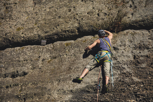 strong young male rock climber with rope, helmet slimbing shoes and other gear on sandstone wall reaching up