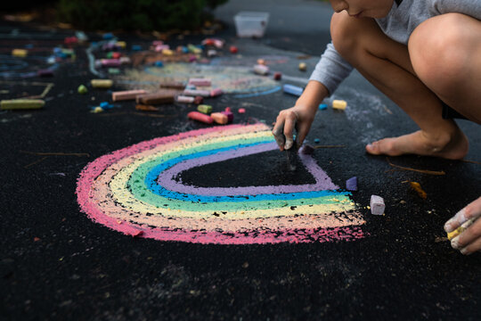 low angle view of young boy drawing rainbow art with chalk on pavement