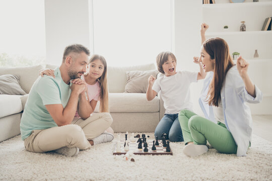Full size profile photo of hooray nice family mom dad two kids play chess win on floor wear t-shirts at home