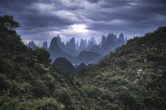 Yangshuo mountains with dark clouds framed by hills, Yangshuo, Guangxi, China
