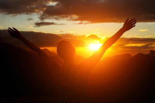 The girl joyfully raised her hands at dawn