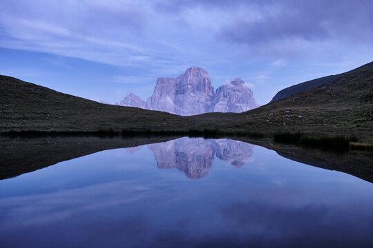 Reflection of Pelmo mountain in the Baste lake during blue hour, Dolomites, Trentino-Alto Adige, Italy