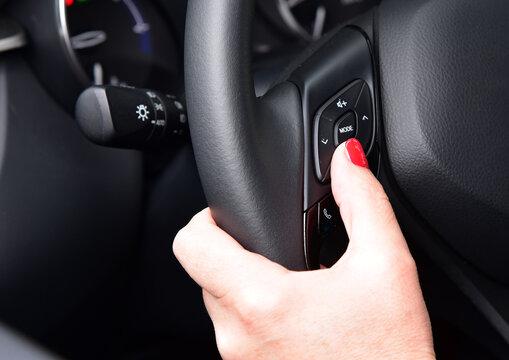 Female finger on volume control button on car steering wheel