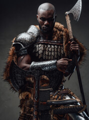 Fototapeta Northern african chief with fur wielding dual axes in dark background