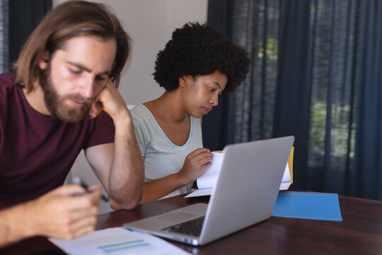 Diverse couple sitting at table working from home, using laptop and checking documents
