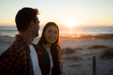 Happy caucasian couple on the beach looking at each other during sunset