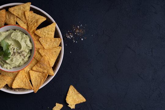 Avocado hummus dip and corn chips on dark gray table, top view
