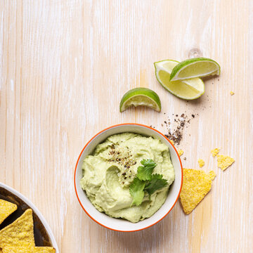 Avocado hummus dip and corn chips on white wood table, top view