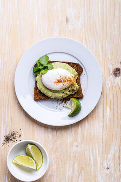 Rye bread avocado hummus toast with poached egg on white plate