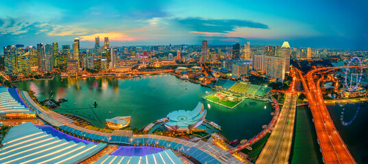 Singapore - May, 2018: Wide panorama at sunset and blue hour of Singapore Marina Bay with illuminated skyscrapers of the financial district in the downtown of the city. Singapore cityscape aerial view
