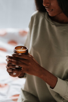 Closeup of an African female holding a glass jar with a handmade scented candle in her room