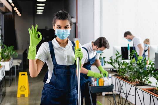 African american worker of cleaning company in medical mask holding mop and showing ok gesture in office