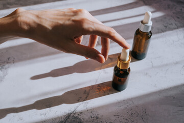 Cosmetic bottles made of dark glass on light concrete pastel surface. Woman's hand holds the cap of one bottle. Spectacular long shadow. Top view, minimalism, copy space. Organic vegan cosmetics.