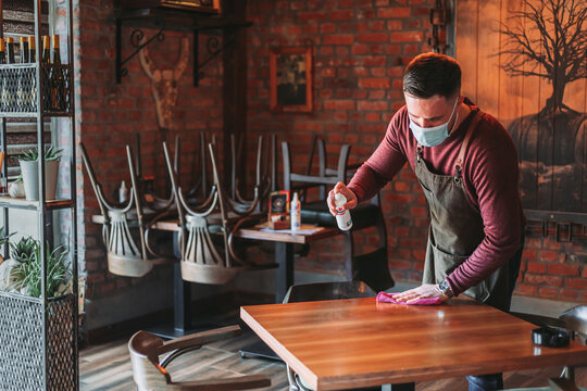 Young waiter disinfecting table in cafe while wearing face mask