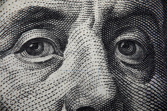 Close-up of benjamin franklins face on hundred banknote