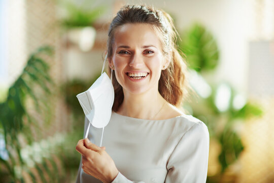 happy modern female in grey blouse taking off ffp2 mask