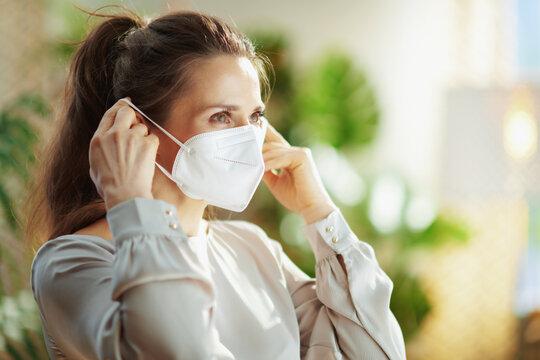 trendy woman in grey blouse wearing ffp2 mask