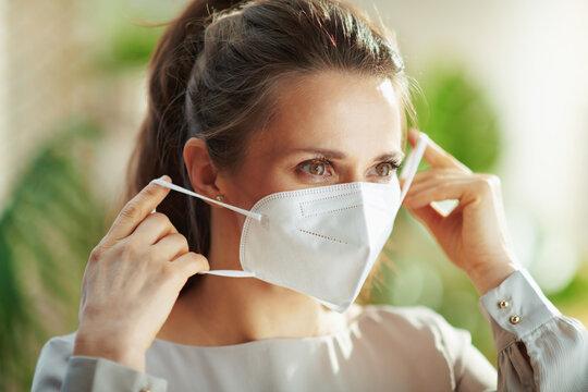 woman in grey blouse wearing ffp2 mask