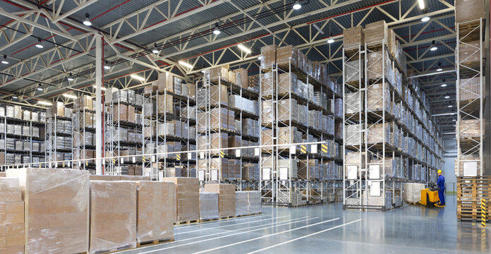 Huge distribution warehouse with high shelves and forklift with young driver.