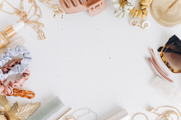 Modern summer accessories flat lay, space for text. Gold jewellery, sunglasses, barrettes, cosmetic