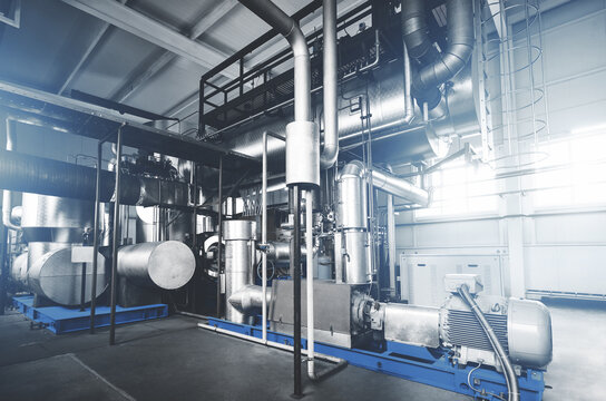 Rankine organic cycle turbine (ORC-turbine) installed in modern industrial boiler room with control cabinets, equiped for heating process. Blue toning