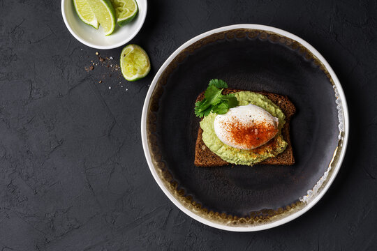 Rye bread avocado hummus toast with poached egg on black plate