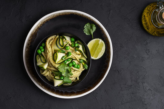 Bowl of linguine pasta with avocado sauce, green peas, zucchini, sprouts on dark grey table