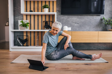 Fit senior woman relaxing at home, sitting on the floor and using tablet.